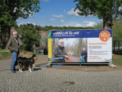 Stadtrat Klaus Sanzenbacher vor Plakat der Entmüllungsaktion